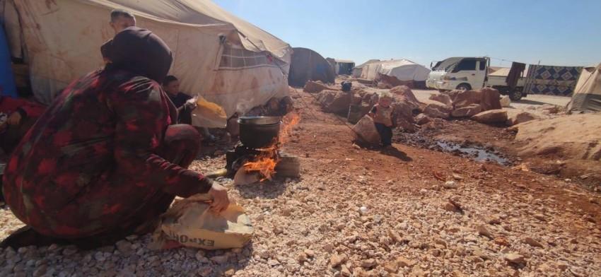 إحدى النازحات تستخدم الأوراق ومواد أولية لطهي الطعام مع عجزها عن شراء أسطوانة غاز.