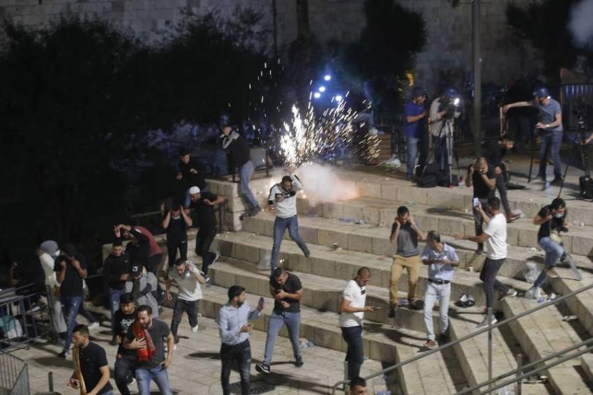 فلسطينيون يحتمون من الرصاص الإسرائيلي عند بوابة دمشق في محيط البلدة القديمة. (أ ب)