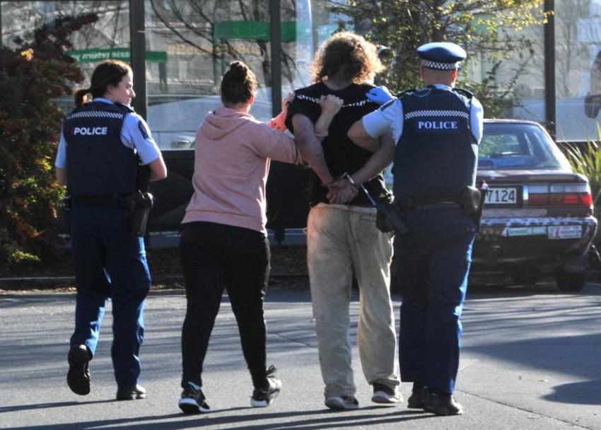 المعتقل أثناء اقتياده لمركز الشرطة. (رويترز)
