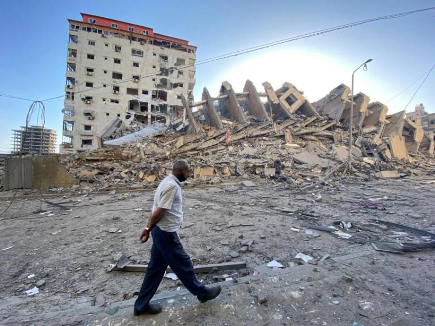 رجل يسير قرب مبنى دمرته الغارات الإسرائيلية في غزة. (رويترز)