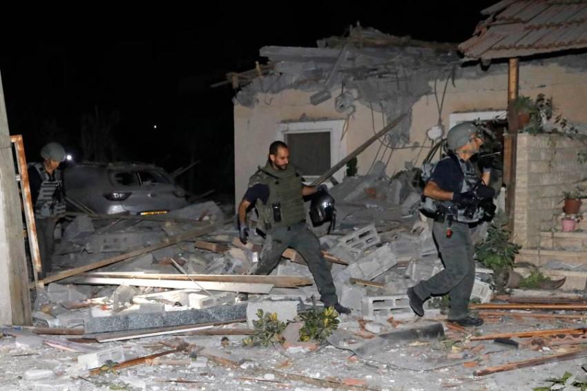 رجال إطفاء إسرائيليون يتفقدون الأضرار في منزل قرب تل أبيب بعد سقوط صاروخ أُطلق من غزة. (أ ف ب)