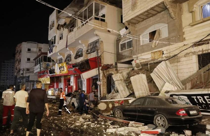 رجال إطفاء وشبان يتفقدون آثار القصف في غزة فجر الأربعاء. (أ ب)