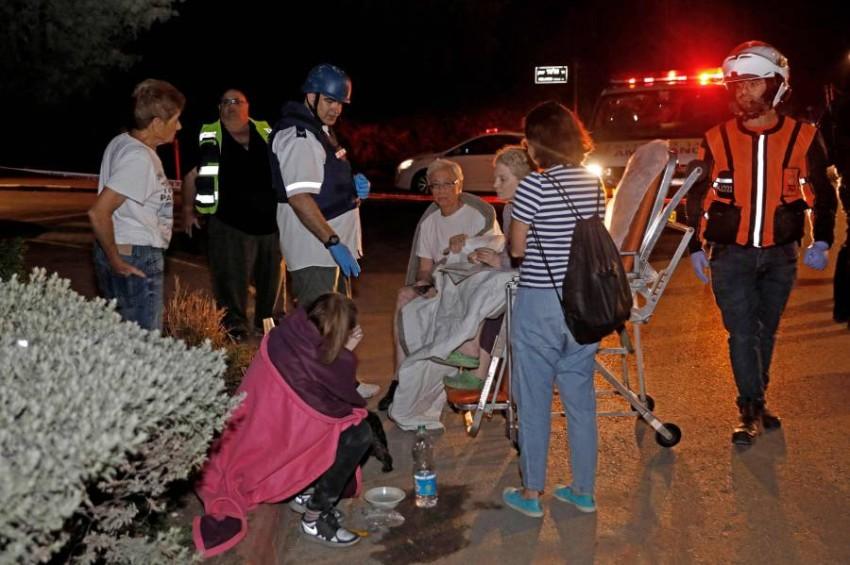 فرق إنقاذ تجلي جرحى إسرائيليين أصيبوا بإصابات طفيفة في يهود قرب تل أبيب. (أ ف ب)