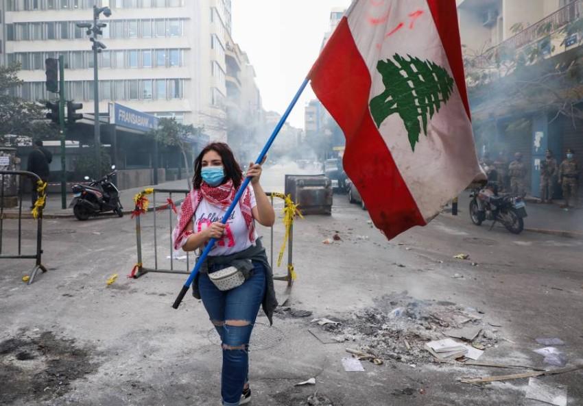 متظاهرة تحمل العلم اللبناني في بيروت. (رويترز)