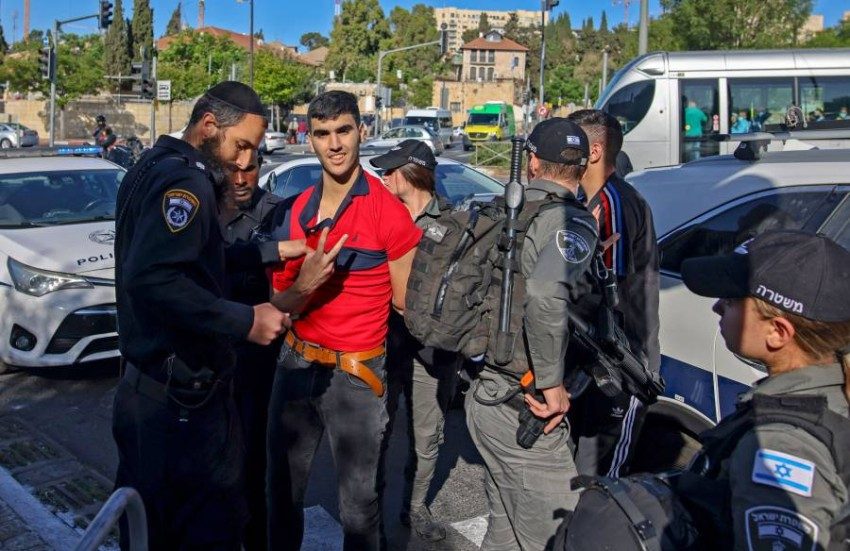 جندي إسرائيلي يعتقل فلسطينياً أمام سور البلدة القديمة. (أ ف ب)