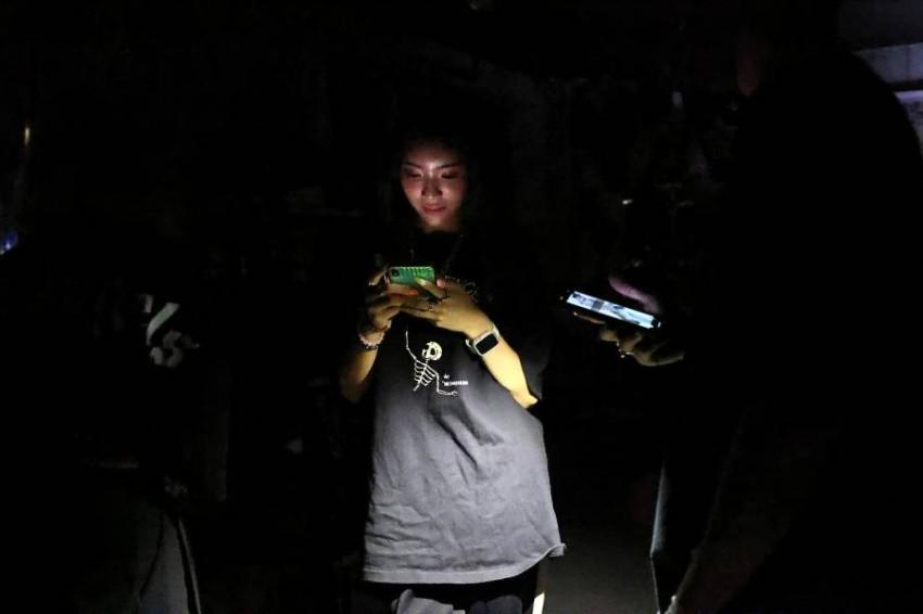 سيدة لجأت لضوء هاتفها المحمول. (رويترز)