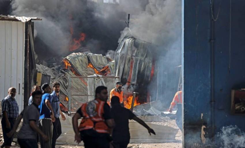 رجال إطفاء فلسطينيون يهرعون لإخماد حريق عقب غارة إسرائيلية. (أ ف ب)