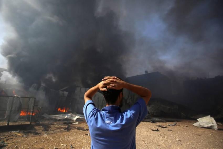 فلسطيني يقف أمام الدمار في مباني ومنشآت غزة. (رويترز)