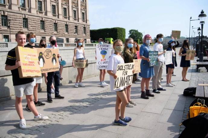 نشطاء يتظاهرون أمام البرلمان السويدي ضد تغير المناخ.(أ ف ب)