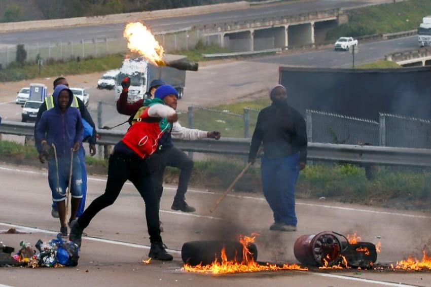 محتجون من مؤيدي زوما يستخدمون إطارات محترقة لقطع طريق سريع. (رويترز)