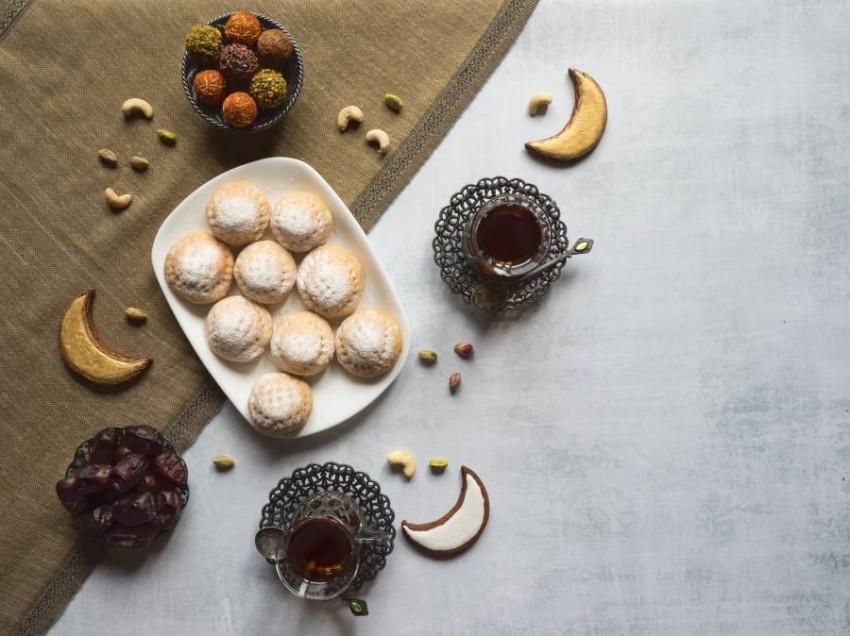 "Arabic sweets celebration Eid Ramadan. Egyptian cookies ""Kahk El Eid"" and tea cups. Top view."