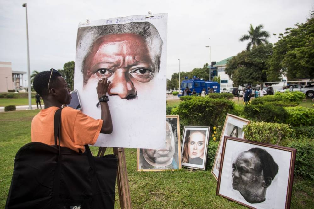 An artist paints a portrait of Kofi Annan at the entrance of Accra International Conference Centre in Accra on September 11, 2018, where the coffin of the Ghanaian diplomat and former Secretary General of United Nations who died on August 18 at the age of 80 after a short illness lays. - Annan's body will remain at Accra Conference Centre until the burial ceremony that will take place on September 13 at Burma Camp military cemetery in Accra. Kofi Annan was the seventh Secretary-General of the United Nations, serving from 1997 to 2006. (Photo by CRISTINA ALDEHUELA / AFP)